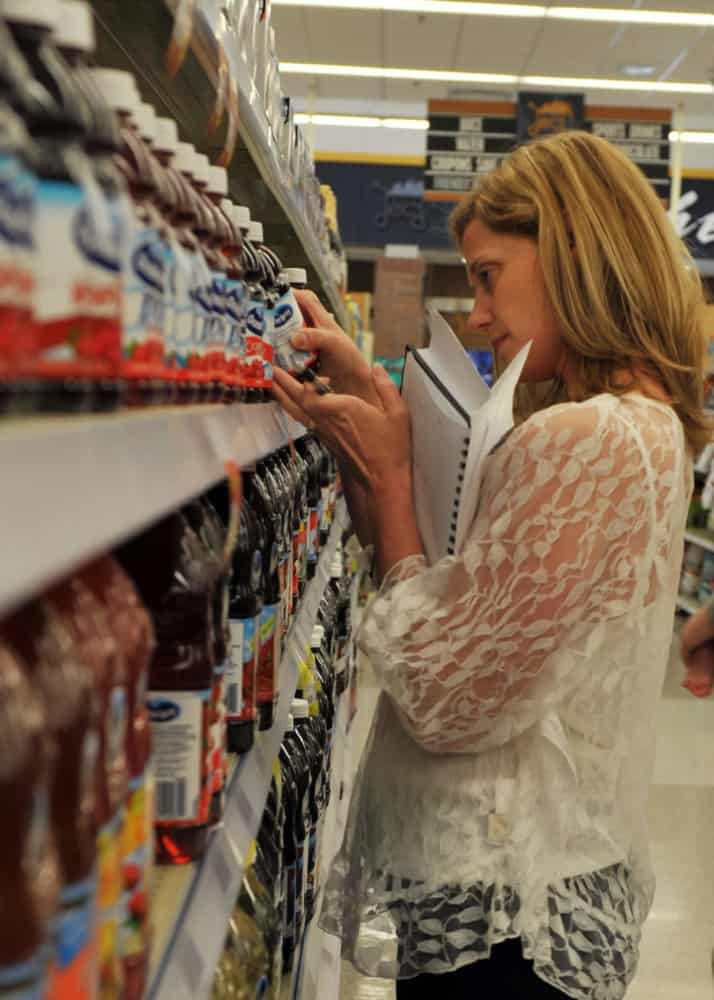 Blonde woman in grocery aisle reading information from a bottle of cranberry juice