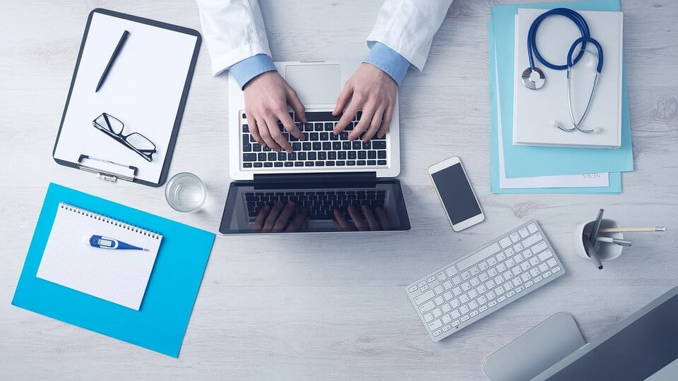 Overview of doctor typing on his laptop, surrounded by tools he uses to practice medicine