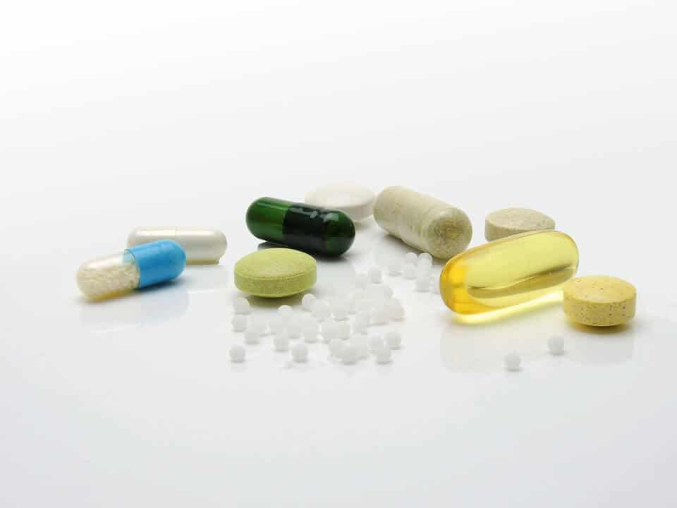 Different variations of pills and supplements spread out on a clear white surface; pressed, gel caps, clear capsules