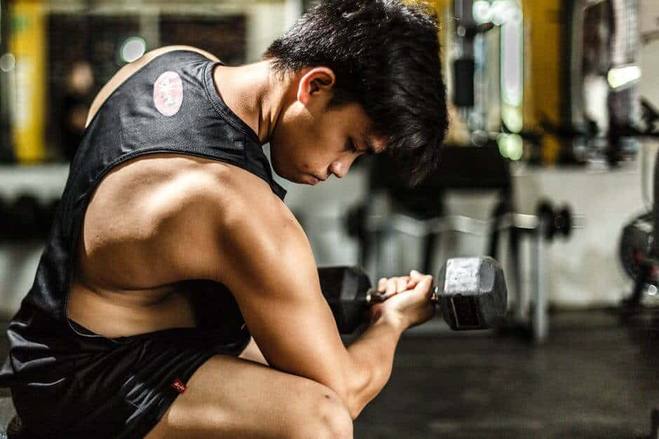 man in tank top doing a concentration curl with right arm