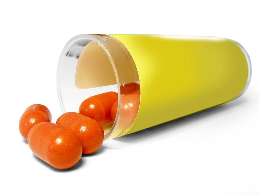 orange pill capsules coming out of plastic bottle with plain yellow label around it