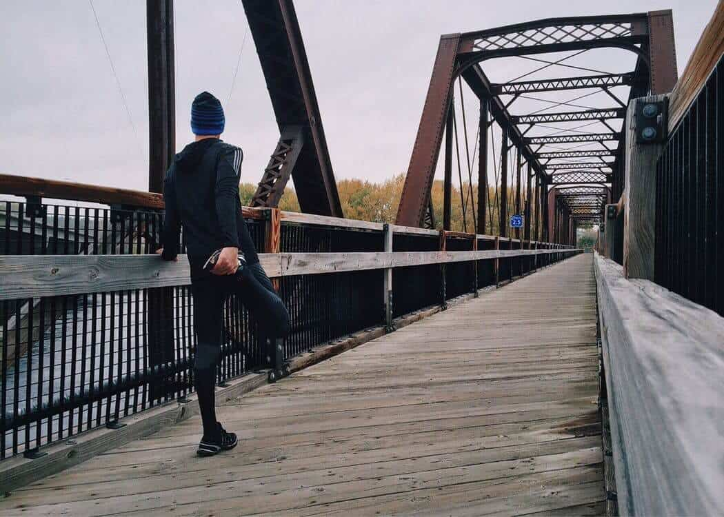 Male runner stretching on a bridge before starting his workout