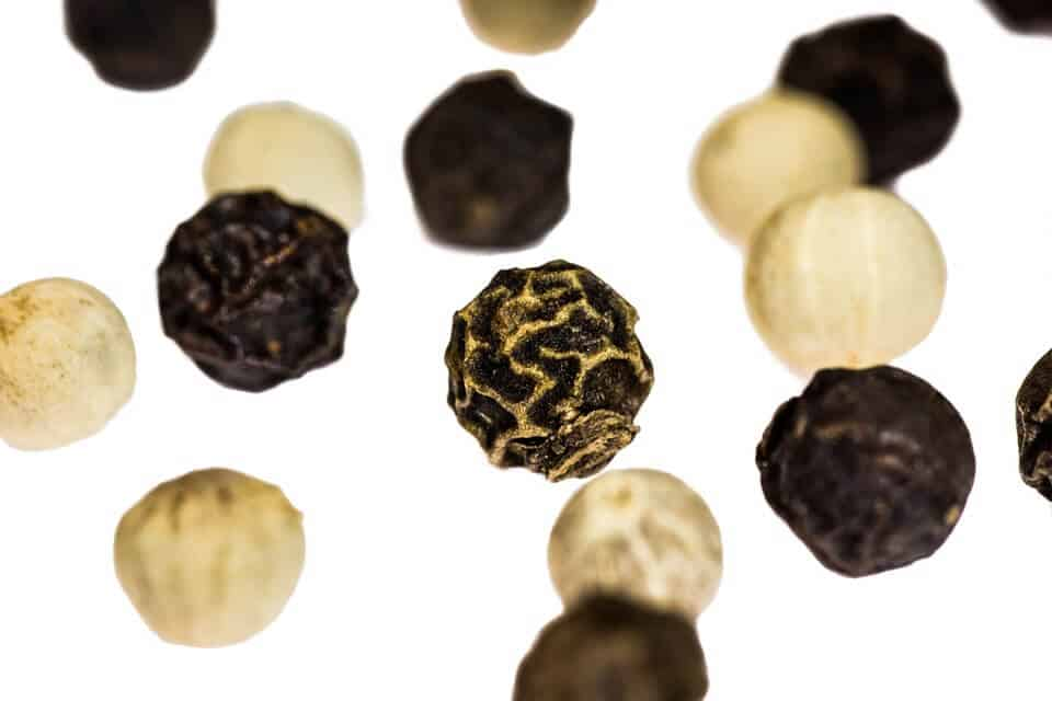 Up close shot of black and white pepper falling