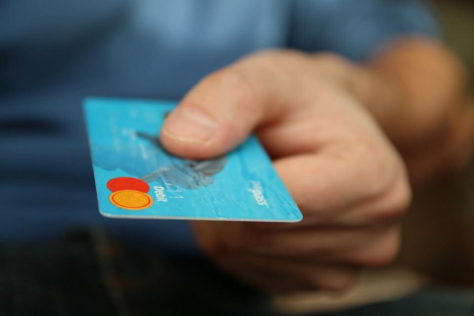 Man handing off a light blue debit card