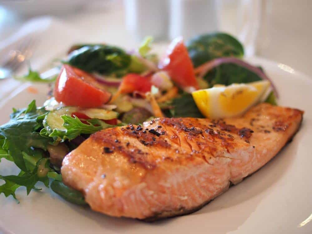 Grilled salmon alongside fresh salad and lemon wedge on a plate