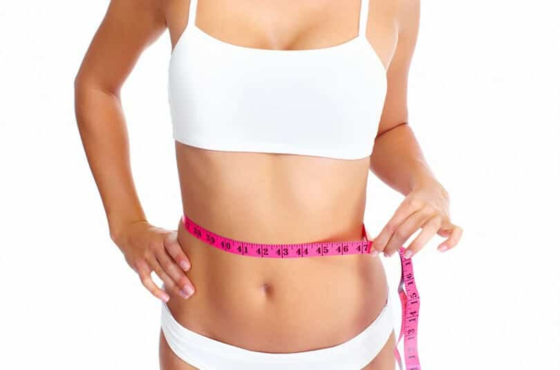 Fit woman in underwear holding pink measuring tape along her waist