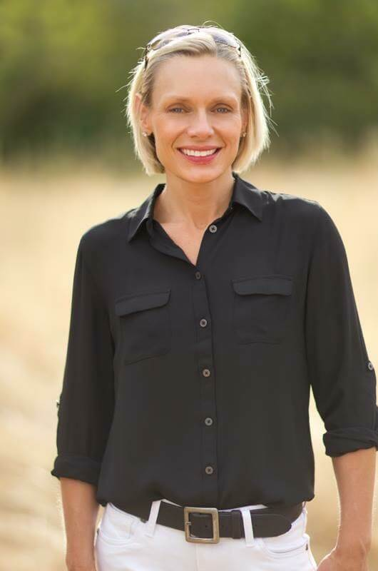 Upper body shot of Ms. Sara Lindberg wearing a black button up shirt, she has short blonde hair