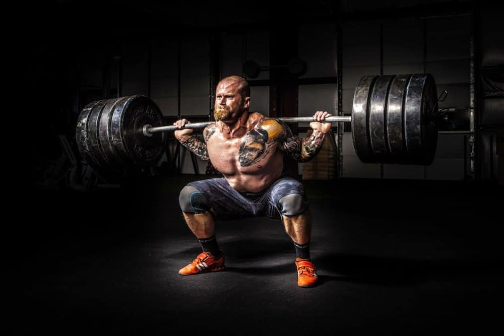 Man squatting heavy barbell in a dimly lit gym