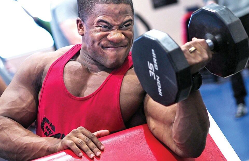 Man in a red tank top doing a preacher curl with his left hand, holding a 35 pound dumbell