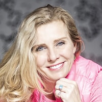 Headshot of Ms. Andrea Metcalf. She is wearing a pink jacke and has blonde hair