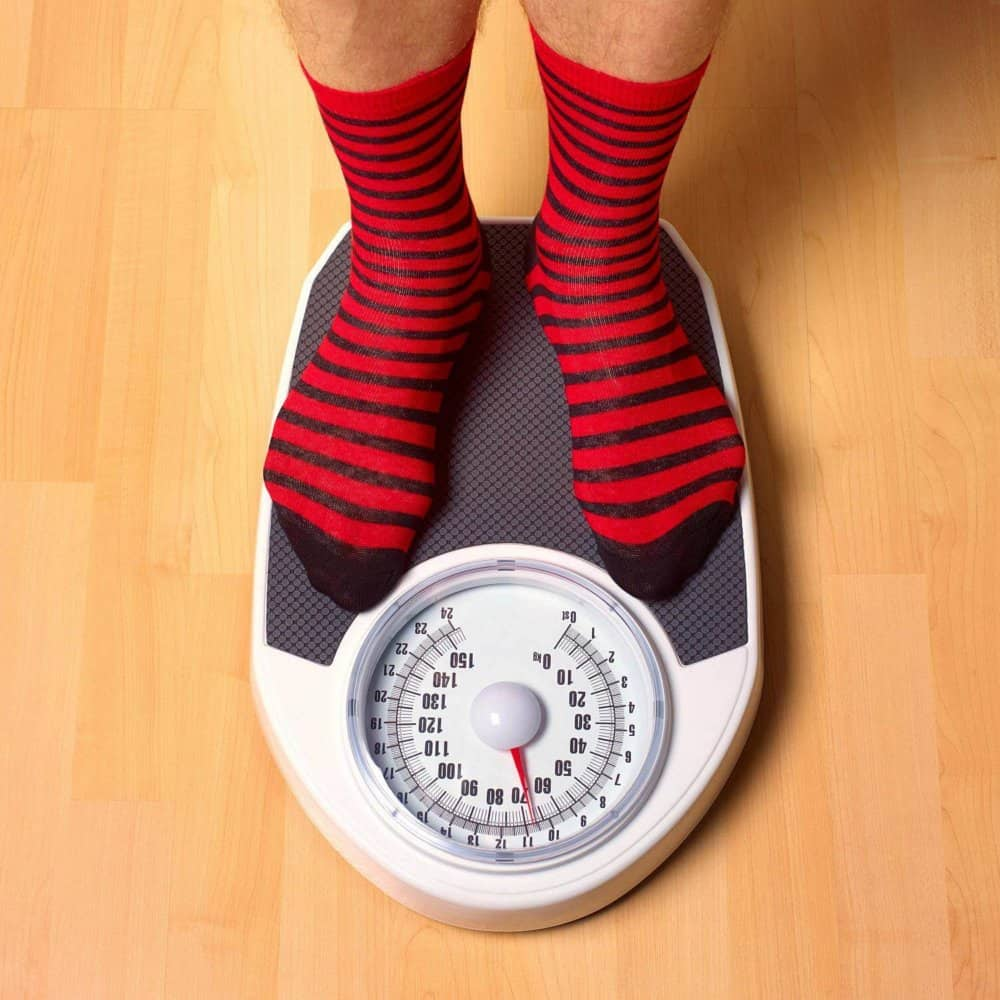 man with red socks and black stripes standing on top of weight scale