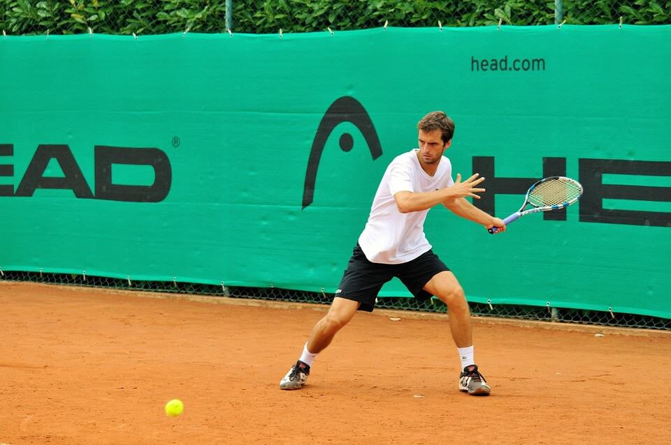 Man in athletic gear playing tennis on a sand court, getting ready to return the ball