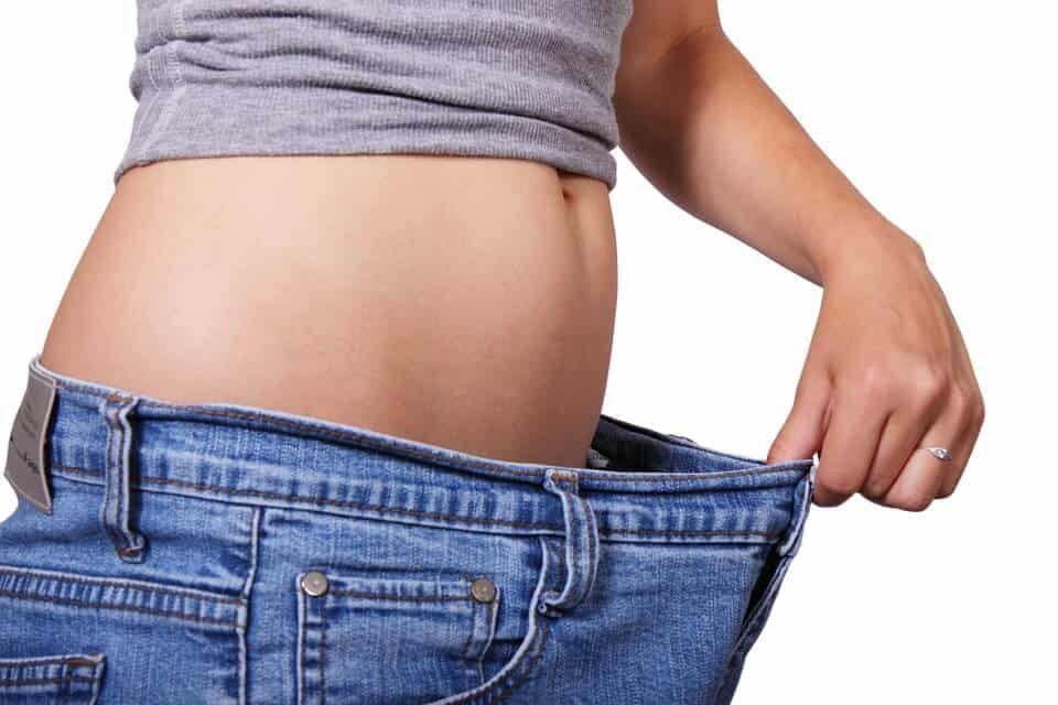 women stretching jeans to the side expressing a drop in pant sizes