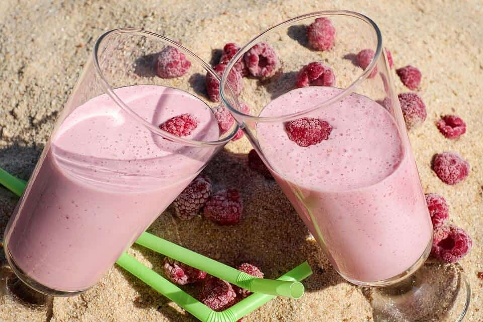 two glass cups on top of sand with a raspberry smoothie inside