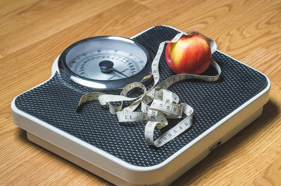 measuring tape and an apple on top of a weight scale