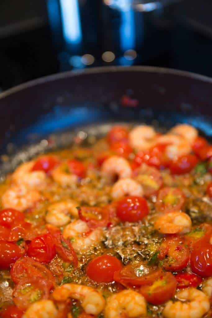 Small shrimp being sauteed in a skillet with cherry tomatoes