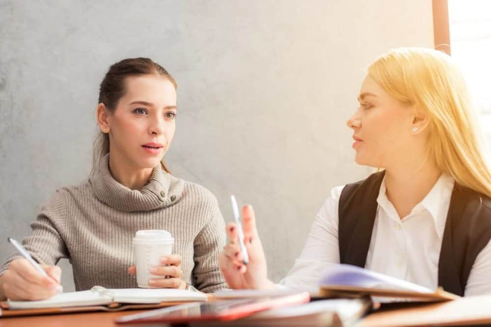 Blonde and brunette in a office conference room conversating