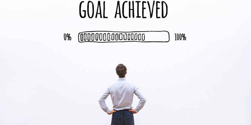 """man in a room looking up at black lettering that reads """"Goal Achieved"""" alongside a fictitious loading bar from 0% to 100%"""