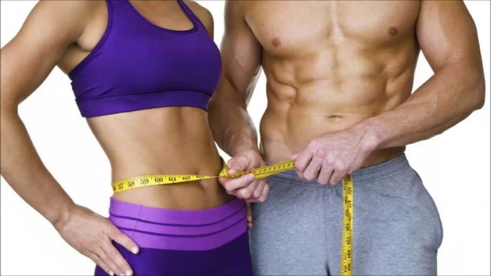 Athletic man holding measuring tape around athletic woman