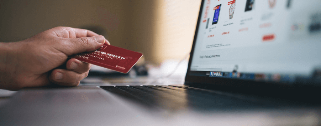man looking at computer screen holding red credit card