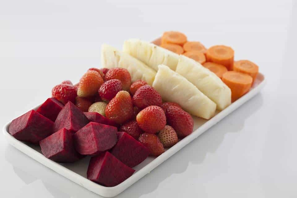 Cut up beets, strawberries, carrots, and pineapple on a white tray