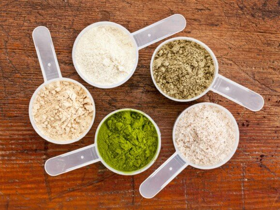 Arrangement of five scoops of different flavors of protein powder