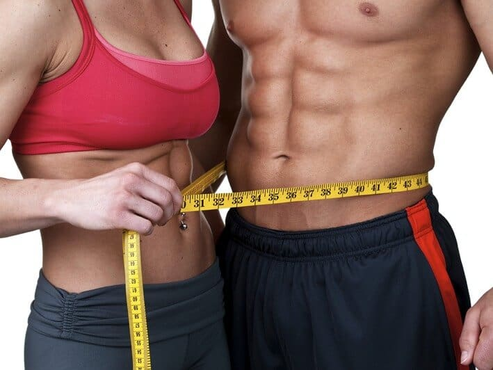 Fit woman in athletic gear holding yellow measuring tape around shirtless fit man