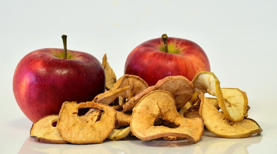 Two fresh apples and slices of dried out apples