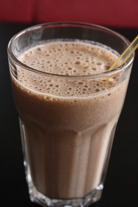Chocolate protein shake in glass cup with a straw