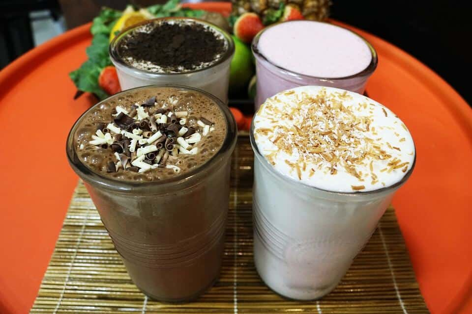 Arrangement of smoothies on an orange tray alongside fruit, flavors are chocolate, vanilla, strawberry, and cookies and cream