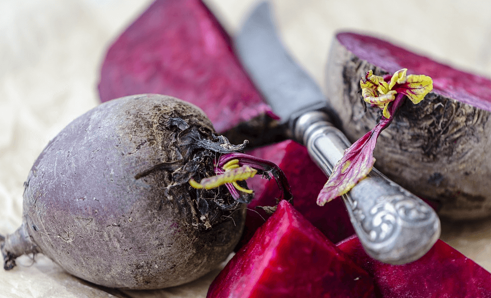 Up close shot of whole beets cut up alonside a knife