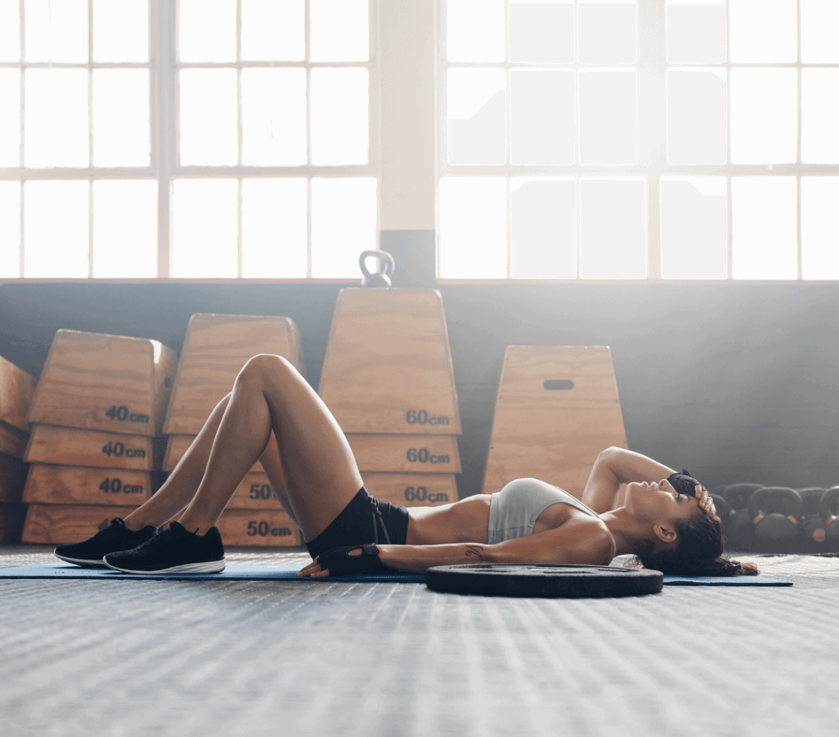 tired woman laying down on a yoga mat inside a crossfit gym