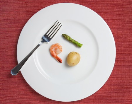 Individual small portions of a potato, one third of an asparagus, and a shrimp next to a big fork on a big white plate