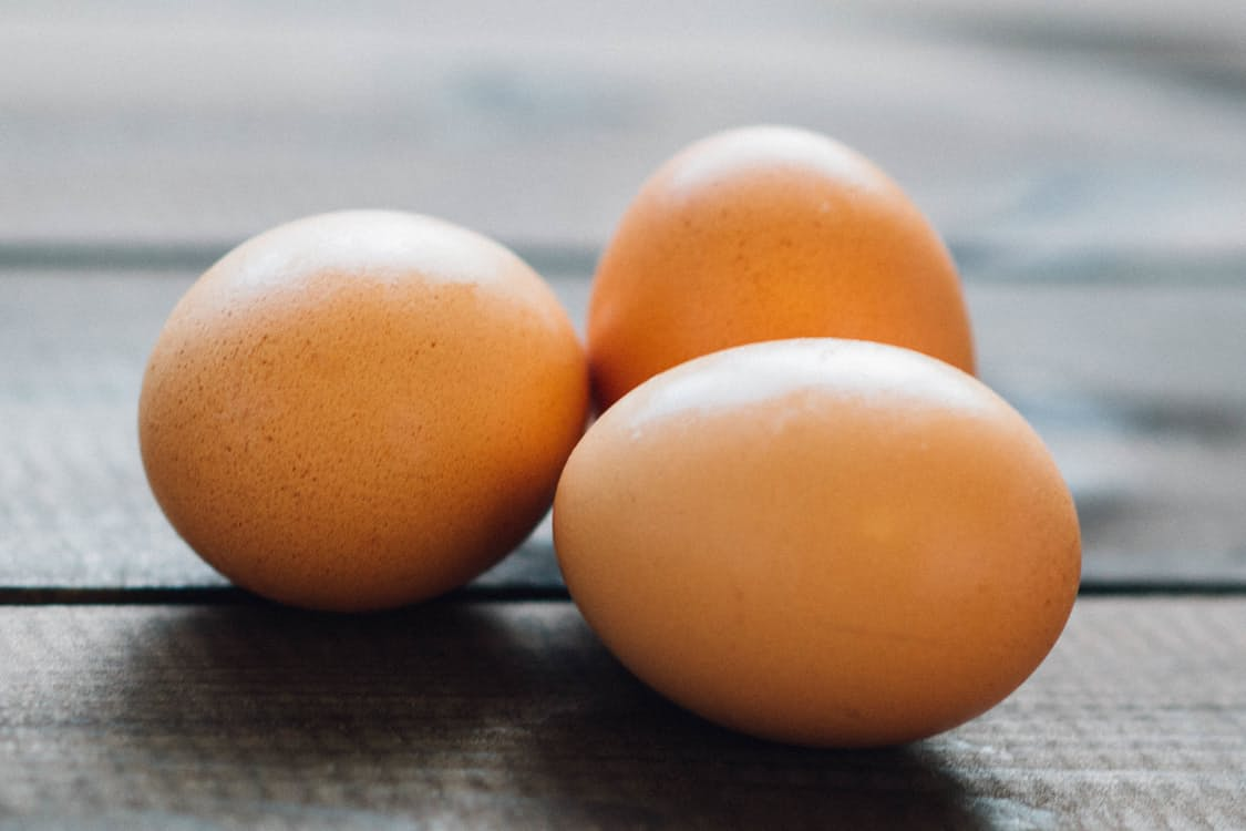 Upclose shot of three organic eggs on wooden picnic table