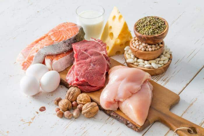 Raw filets of salmon, steak, and chicken on top of a wooden cutting board. Surrounded by dairy products and legumes.