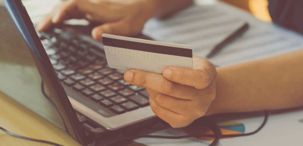 man holding credit card entering number in computer
