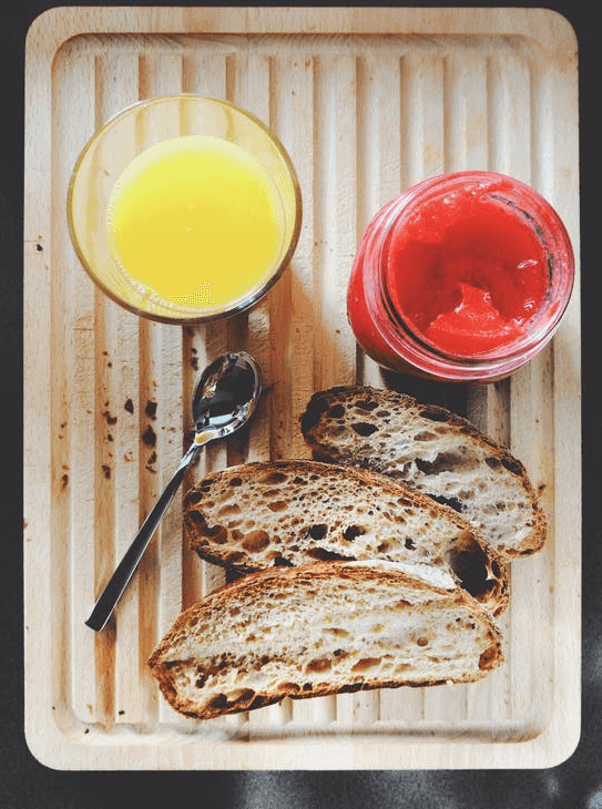 Glass of orange juice, strawberry jam, and toasted bread on top of a wooden board